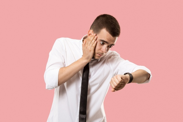 Handsome businessman checking his wrist-watch isolated on pink. wow. attractive male half-length front portrait